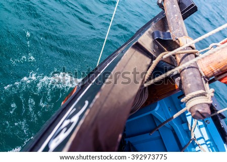 bow and wooden hull of a vintage sailing boat with the bowsprit, mast, ropes and the sea at the background during a sunny sea trip - stock photo
