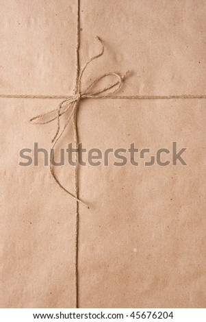 Bow from a cord on a brown packing paper - stock photo