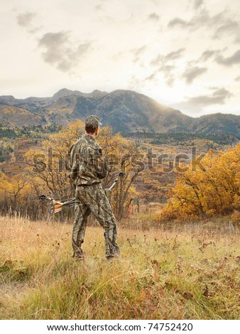 bow hunter man dressed in camouflage in the mountains at sunrise - stock photo