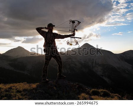 bow hunter silhouette with dramatic landscape - stock photo
