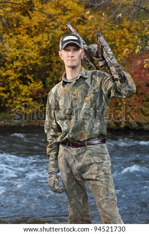 bow hunter standing by river in fall - stock photo