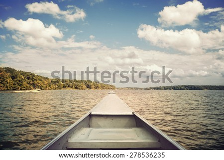 Bow of a canoe on a lake. Focus on bow.  Vintage effect. - stock photo