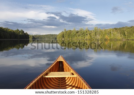 Bow of a Cedar Canoe on a Tranquil Lake - Ontario, Canada - stock photo
