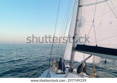 Bow of yacht with hoisted sails cruising on North Sea alongside the Netherlands coast at twilight time on a summer evening - stock photo