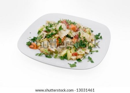 Bow tie pasta salad on plate isolated on white with clipping path. Salad has chick peas, carrots, summer squash, red pepper and parsley. - stock photo