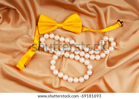 Bow ties and pearl necklace on the satin - stock photo