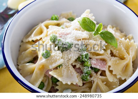 Bow ties pasta with ham, green peas and parmesan - stock photo