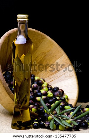 bowl and bottle of olive oil with olive branch on burlap background - stock photo