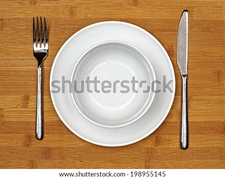 Bowl and plate with fork and knife on a bamboo wood background - stock photo