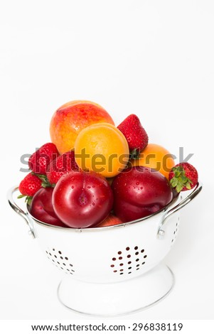Bowl colander full of fresh delicious fruits isolated on white background