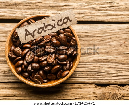 Bowl full of Arabica coffee beans over an old wooden table - stock photo