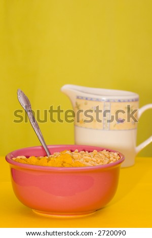 Bowl full of cereal with milk on the side
