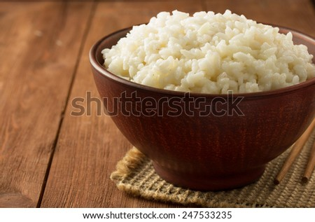 bowl full of rice on wooden background - stock photo