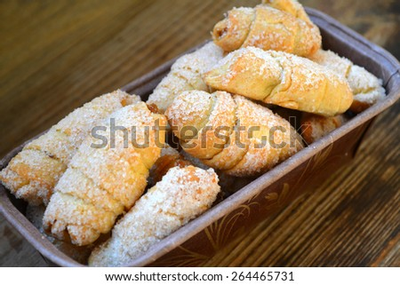 Bowl full of small French croissants covered in sugar on wooden table - stock photo