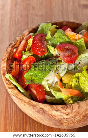 Bowl made of olive wood filled with cos and iceberg lettuce salad with paprika, carrots, tomatoes and green olives on wooden table. More healthy food in my portfolio - stock photo