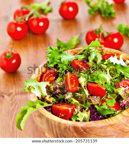 Bowl made of olive wood filled with mixed lettuce salad and cherry vine tomatoes on wooden table. More healthy food in my portfolio - stock photo