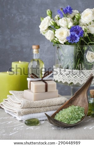 Bowl od green sea salt, bars of handmade soap, essential oil and scented candles - stock photo