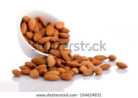 Bowl of almonds isolated on white background - stock photo
