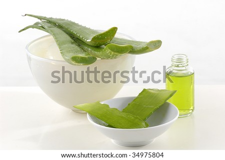 Bowl of aloe with aloe cosmetics in background - stock photo