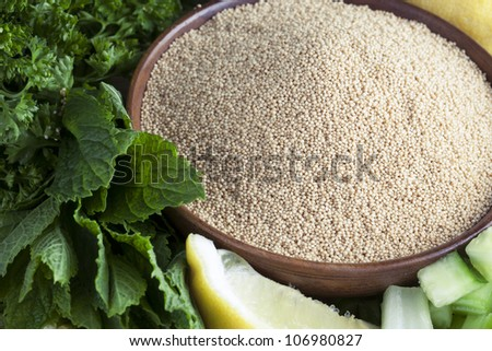 Bowl of amaranth seeds surrounded by mint, parsley and a lemon wedge.