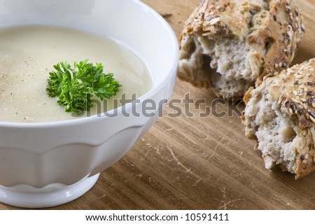 bowl of asparagus soup with chervil on wooden table. Grainy bread on background.  Health food. - stock photo
