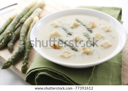 Bowl of asparagus soup with croutons on white background - stock photo