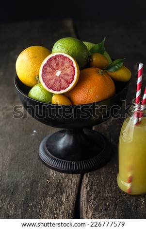 Bowl of assorted fresh citrus fruit with a halved blood orange with its distinctive red pulp in the foreground with a bottle of freshly squeezed orange juice - stock photo