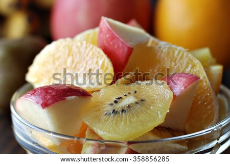 Bowl of assorted fresh fruits : Apple, oranges, kiwi and banana in a glass bowl on a wooden table. - stock photo