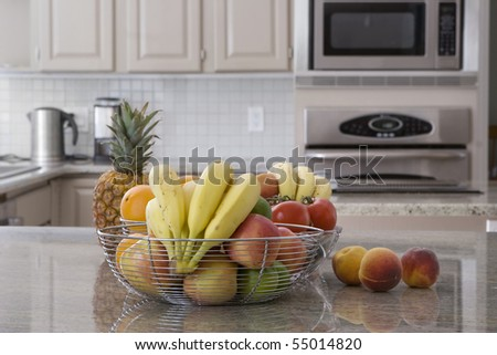 bowl of assorted fruit in modern grey kitchen - stock photo
