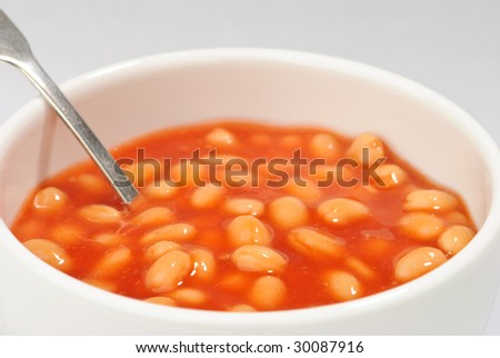Bowl of baked beans in tomato sauce with spoon - stock photo