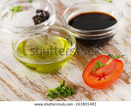Bowl of Balsamic vinegar and olive oil on a wooden table. - stock photo