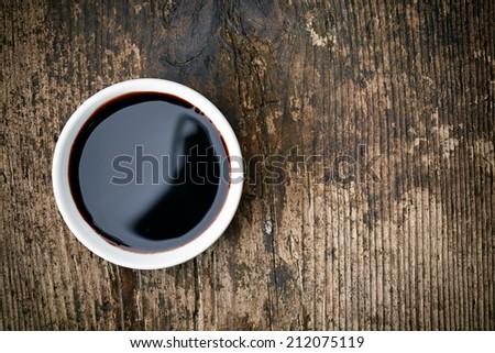 Bowl of Balsamic vinegar on wooden table - stock photo