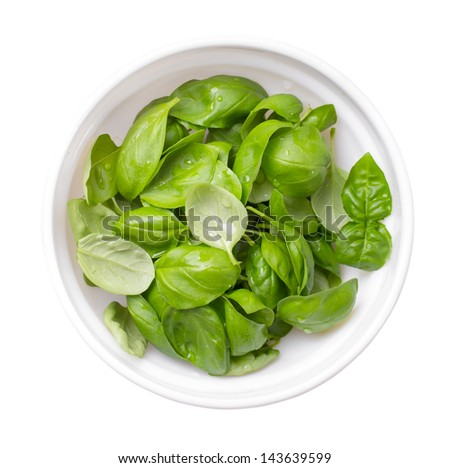 Bowl of basil leaves isolated on white top view - stock photo