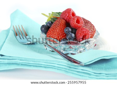 Bowl of berries with strawberries, raspberries and blue berries with serving fork and pale aqua blue napkin closeup. - stock photo