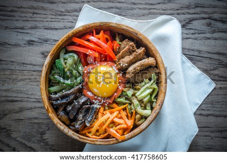 Bowl of bibimbap on the wooden table - stock photo
