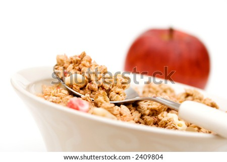 Bowl of breakfast cereal and red apple