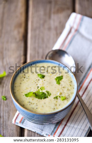 Bowl of broccoli and cheddar cheese soup served in blue crockery bowl on wooden table - stock photo