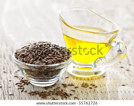 Bowl of brown flax seed and linseed oil - stock photo