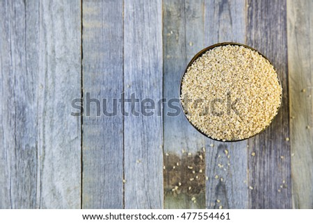 Bowl of bulgur and rolled oats in a row viewed from above on an old wooden table, with copy space