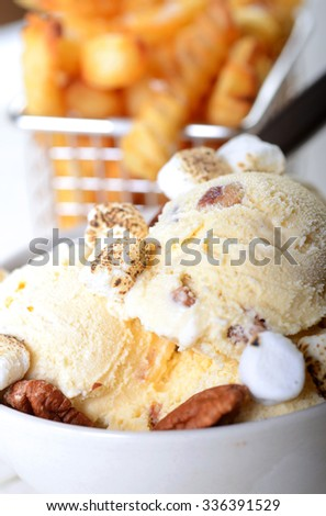 Bowl of Butter Pecan Ice Cream with whole pecans and toasted marshmallows with crispy French Fries - stock photo