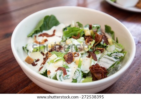 Bowl of Caesar Salad on wooden table - stock photo