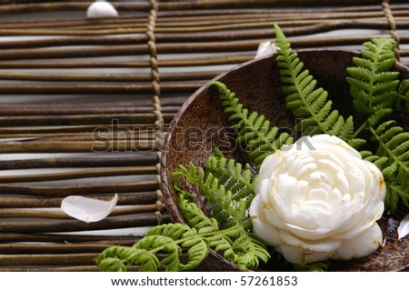 bowl of camellia blossoms on mat - stock photo