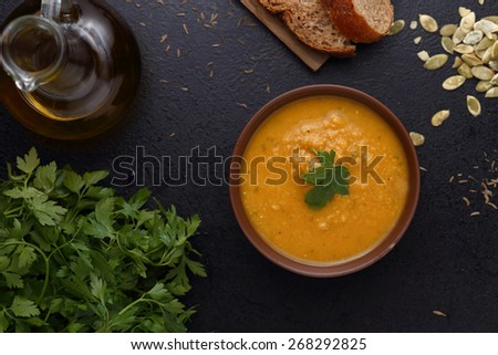Bowl of carrot and pumpkin soup, piece of bread and green on dark background. Top view - stock photo