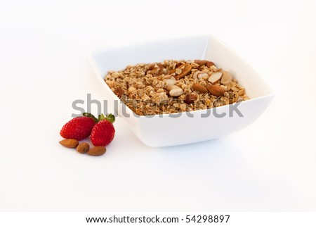 Bowl of cereal, strawberries and almonds over white - stock photo