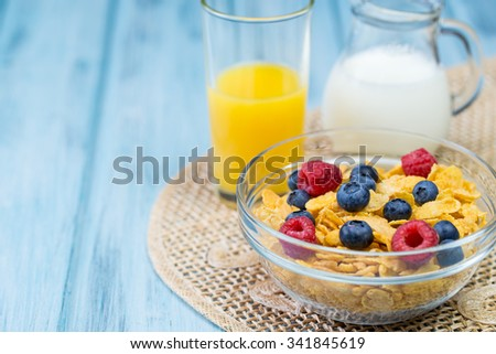 Bowl of cereal with berries, glass of orange juice and jug of milk