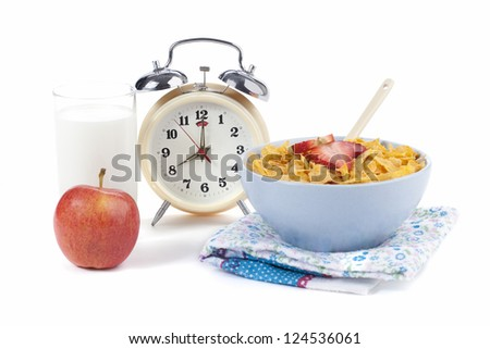 Bowl of cereals placed beside an alarm clock with glass of milk and apple