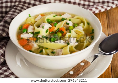 Bowl of chicken noodles soup  on a old wooden table. Selective focus - stock photo
