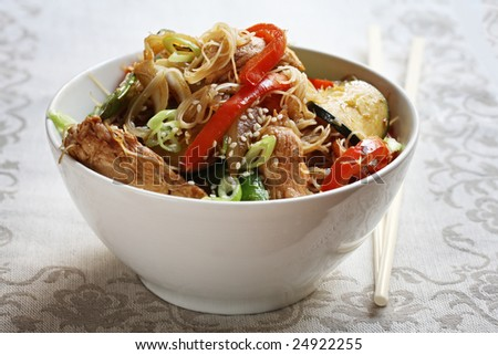 Bowl of chicken or pork stir-fry, with vegetables and rice noodles. - stock photo