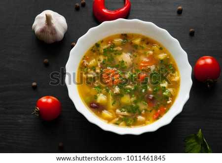 Bowl of chicken soup with noodle and vegetables on a dark wooden background