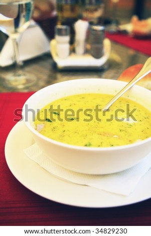 Bowl of chicken soup with selective focus and utensils on background - stock photo